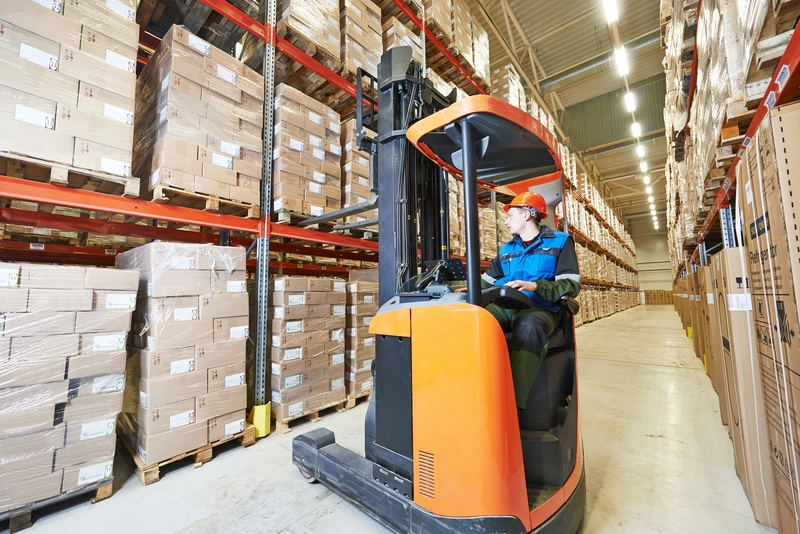 Warehouse forklift stacker loader stacking card boxes in storehouse